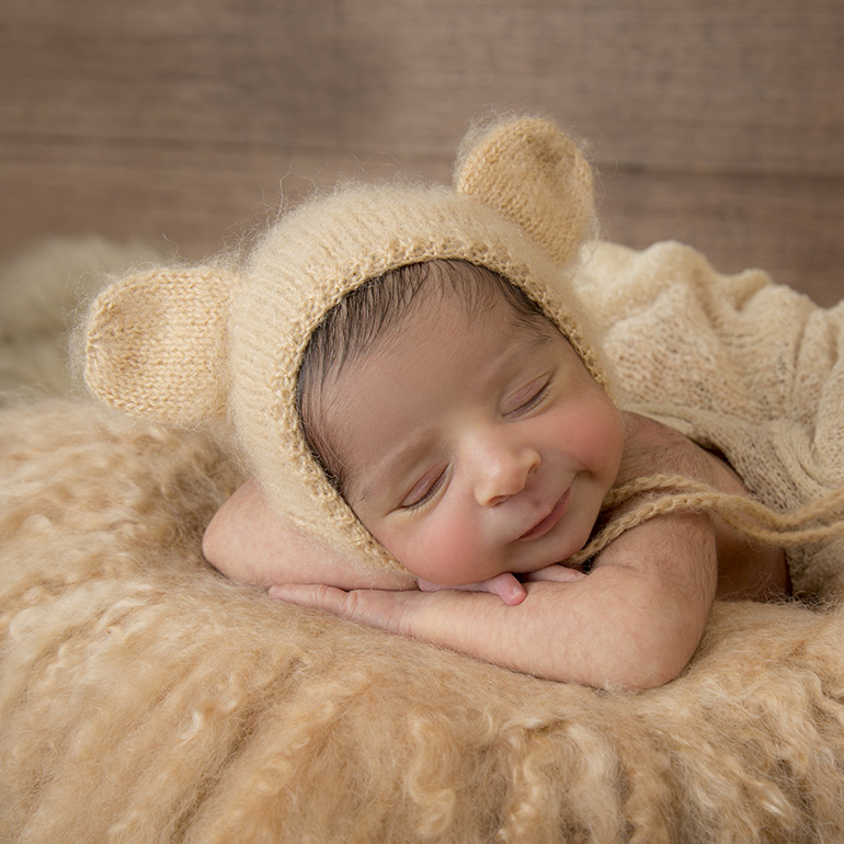 Newborn baby boy wearing a beige bear hat on brown fur