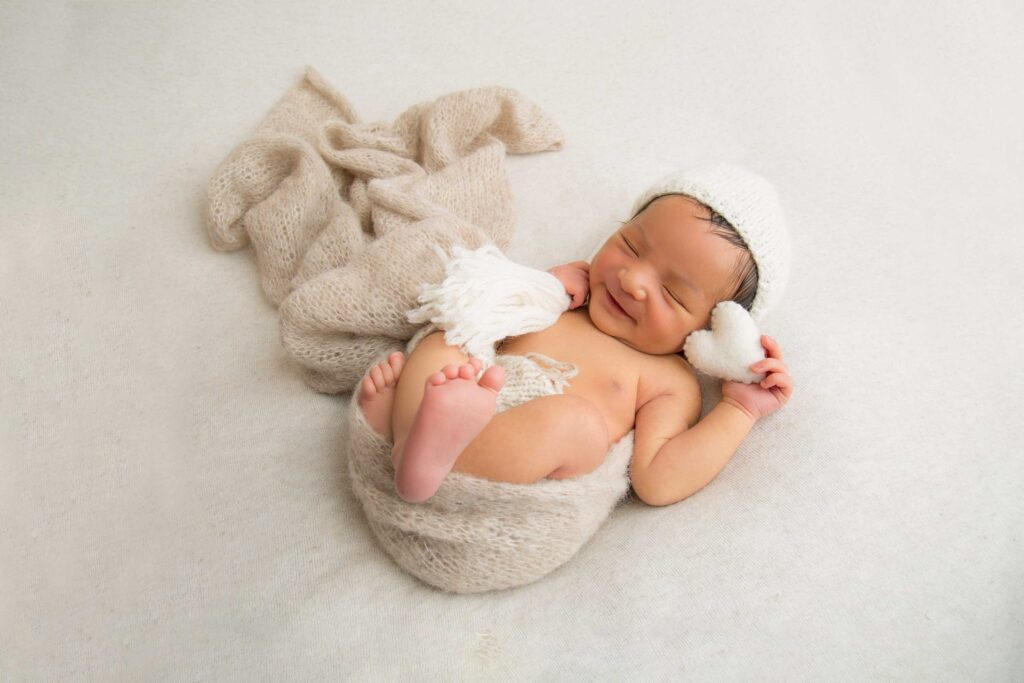 Cute baby boy wrapped in beige blanket ready for photo shoot