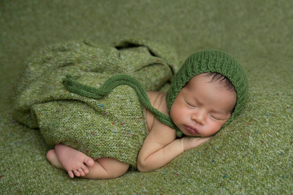 This beautiful newborn baby is ready to get photographed in his green outfit