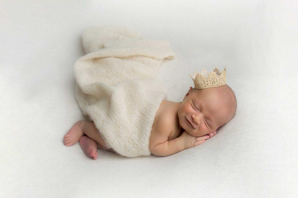 Sleeping newborn baby wrapped in beige wearing a gold crown