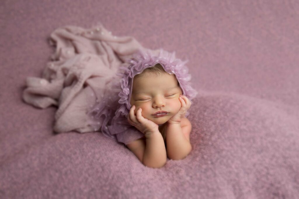 Newborn baby girl with a purple bonnet on a purple background