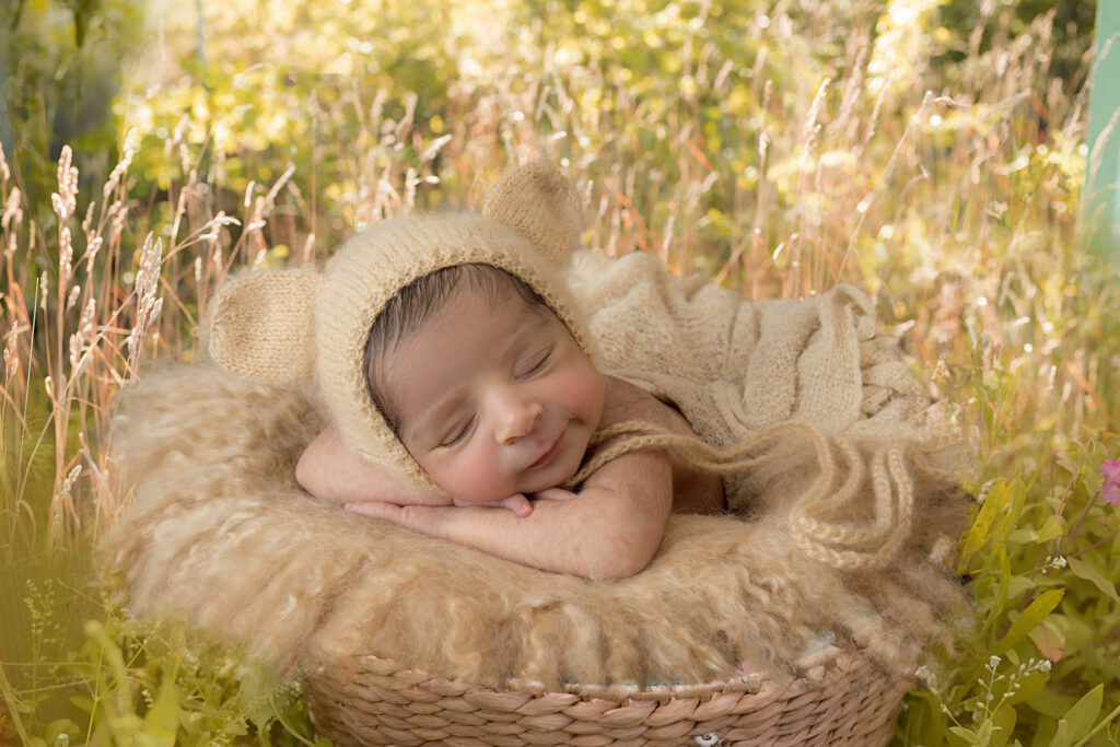 Beautiful newborn sleeping in a basket in a grass field ready for newborn photography