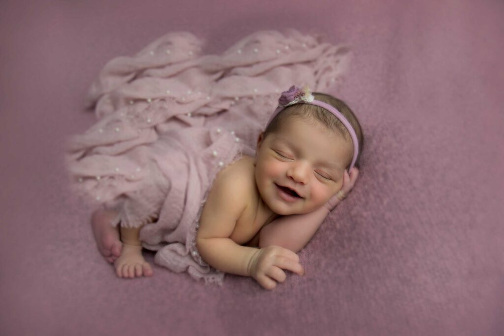 Sleeping baby girl laughing while getting photographed on her purple outfit